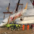 Stricken plane that came off the runway is lifted from slope